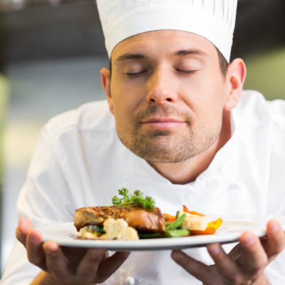 Closeup of a male chef with eyes closed smelling food in the kitchen